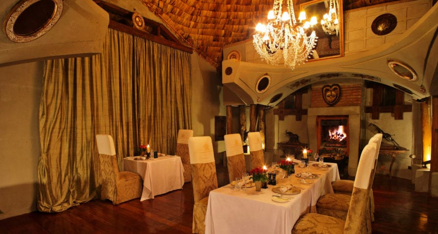 Dine by a cosy fireplace at &Beyond Ngorongoro Crater Lodge. © &Beyond